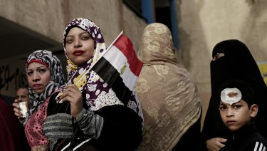 Women wait in line to vote outside a polling station at a school in Giza.