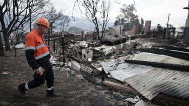 An electricity worker inspects properties on Wildlife Drive in Tathra after the bushfire.