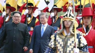 The pair walk together through a honour guard.