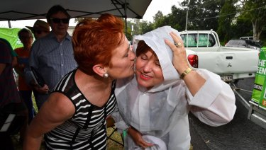 Labor MP Jo-Ann Miller greeted One Nation leader Pauline Hanson with a hug and some booties for her new grandson, despite Labor's attempts to link the resurgent party with the LNP.