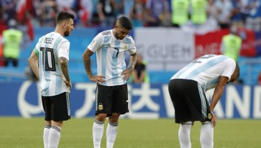 Lionel Messi, left, Ever Banega, center and Gabriel Mercado stand dejected after being eliminated from the World Cup.