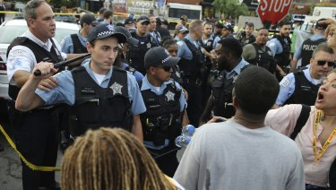 Members of the Chicago Police Department interact with an angry crowd at the scene of a police-involved shooting.