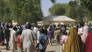 People gather outside the hospital where the released girls were being treated in Dapchi.
