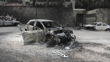 Cars were destroyed by the wildfires near the village of Neos Voutzas near Athens.