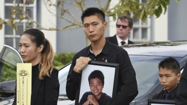 Jason Wang, centre, holds a picture of his brother Peter, who was a victim in the Parkland, Florida school shooting.