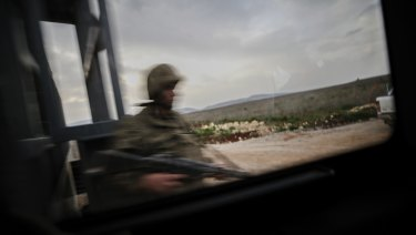 A Turkish soldier secures the border with Syria, in the outskirts of the border town of Kilis, on Saturday.