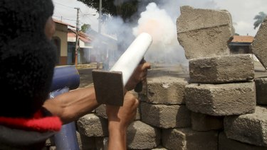 An anti-government protester fires a homemade mortar at the police from a barricade.
