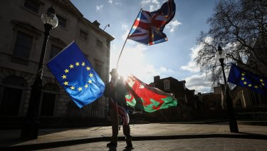 Brexit protesters wave EU flags as well as a British Union Jack, and a national flag of Wales, outside Parliament in London, on Monday.