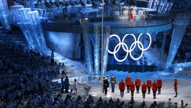 Members of the Royal Canadian Mounted Police and armed forces raise the flag as the national anthem is played at the opening ceremony of the 2010 Winter Olympics in Vancouver.