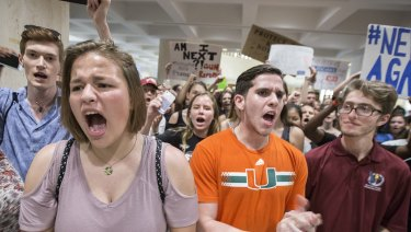 Students chant protest slogans outside the Florida House of Representatives chamber inside the Florida Capitol.