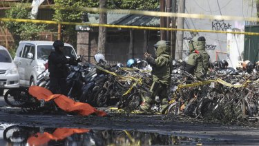 Members of police bomb squad inspect wreckage of motorcycles at the site where an explosion went off outside a church in Surabaya, East Java, Indonesia.