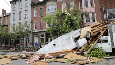 Men stand near buildings damaged by a storm in Newburgh, New York on Wednesday.