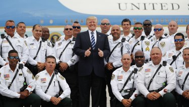 Not quite thumbs up yet: Donald Trump is enthusiastic about North Korea. Here he poses with police officers before boarding Air Force One during his departure from Palm Beach .