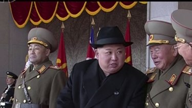 In this image made from video by North Korea's KRT, leader Kim Jong-un speaks with military officials during a parade in Pyongyang.
