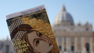 """Pope Francis' book on """"Fake News"""" in front of St Peter's Basilica in Rome."""