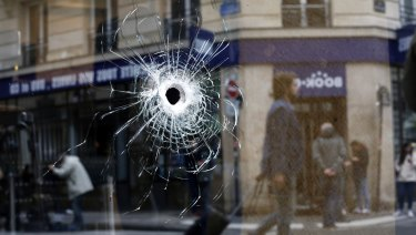 A bullet hole seen on the window of a cafe located near the area where the assailant of a knife attack was shot dead by police officers, in central Paris on Sunday.