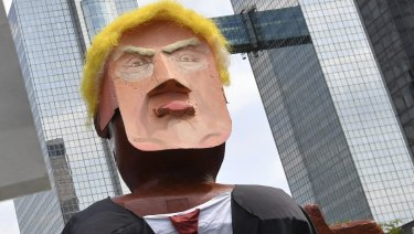 People march with a giant puppet of U.S. President Donald Trump during a demonstration in Brussels,