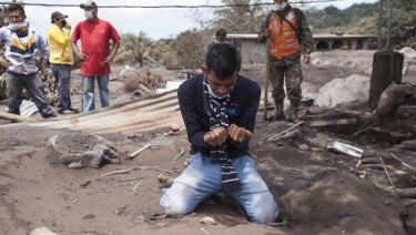 Bryan Rivera cries after looking at the remains of his house in San Miguel Los Lotes, after his family went missing after the eruption.
