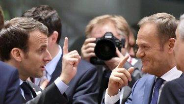 We're in: French President Emmanuel Macron, left, speaks with European Council President Donald Tusk in Brussels.