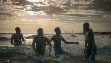 Highly commended by the Moran Prize judges, Matthew Abbott's Wrestlers Cooling Off depicts young South Sudanese men at a beach in Melbourne.