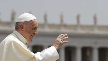 Pope Francis waves to faithful