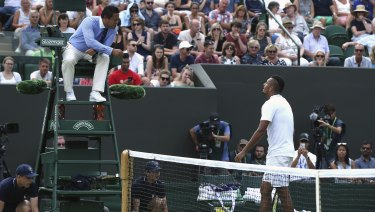 Kyrgios receives a warning for bad language from umpire James Keothavong as he plays Robin Haase.