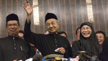 Newly-elected Mahathir Mohamad, centre, waves next to Deputy Prime Minister Wan Azizah, right, in Kuala Lumpur on Friday.