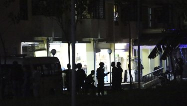 Indonesian police stand guard in front of an apartment building after an explosion.