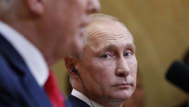 Russian President Vladimir Putin listens to US President Donald Trump