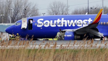 The Southwest Airlines plane sits on the runway with a damaged engine on the left side.