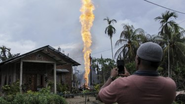 A man takes photos of a burning oil well after it caught fire in Pasir Putih village in eastern Aceh, Indonesia.