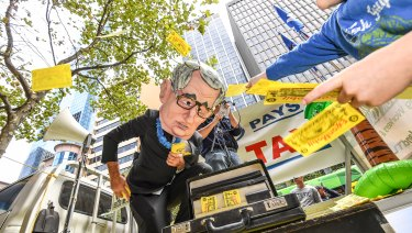 Tax campaigners rally outside a Senate inquiry into resources.