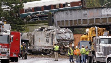 Cars from an Amtrak train lay spilled onto Interstate 5 below as some train cars remain on the tracks above Monday in DuPont, Washington.