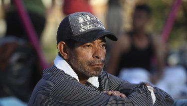 "A man sits amidst other sleeping migrants at a sports club where Central American migrants travelling with the annual ""Stations of the Cross"" caravan are camped out, in Matias Romero, Oaxaca State, Mexico."