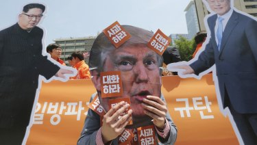 A protester wearing a mask of US President Donald Trump, centre, performs with cut-out photos of North Korean leader Kim Jong-un and South Korean President Moon Jae-in, right, during a rally against the US in Seoul on Friday.