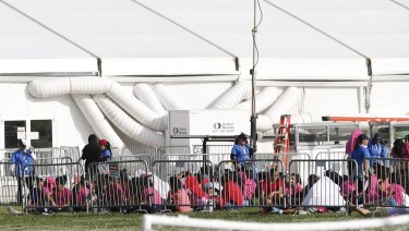 Migrant children sit outside a former Job Corps site that now houses them in Homestead, Florida.