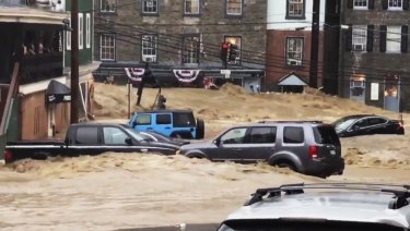 Water rushes through Main Street in Ellicott City, Maryland.