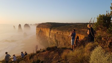 Tourists at the Twelve Apostles ignoring safety barriers to get a better view.