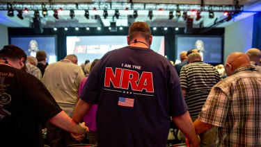 Members of the National Rifle Association (NRA) hold hands during an opening prayer at the NRA annual meeting in Dallas, Texas