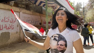 A Sisi supporter wears a T-shirt with his picture as she chants national songs in front of a polling station in Cairo on Monday.