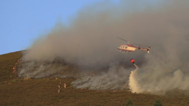 A helicopter drops water as firefighters tackle the wildfire on Saddleworth Moor, England, on Wednesday.