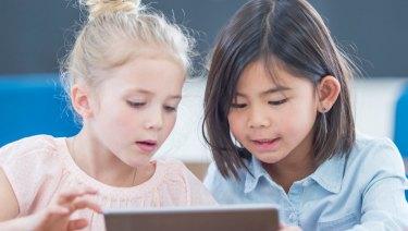 Primary school children use a digital tablet at school.