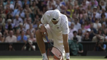 An exhausted Isner kneels after stumbling as he returned the ball to Anderson.
