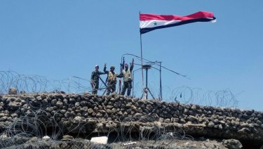 Syrian troops flash the victory sign next to the Syrian flag in Tell al-Haara, the highest hill in the southwestern Daraa province, Syria.