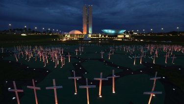 Crosses depicting people murdered for defending the forest stand on a large map of the Amazon, in Brasilia, last year.