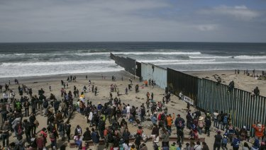 Hundreds of migrants from Central America who travelled in a caravan through Mexico gather with supporters at the border wall where it ends at the Pacific Ocean, in Tijuana, Mexico, on April 29.