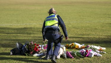 A female police officer laying a white rose among the other tributes.