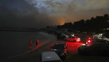 People stand in the sea near to cars parked on the beach to protect them from the fire in the town of Mati.