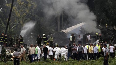 Cuba's President Miguel Diaz Canal, third from left, walks away from the site where a Boeing 737 plummeted into a yuca field.
