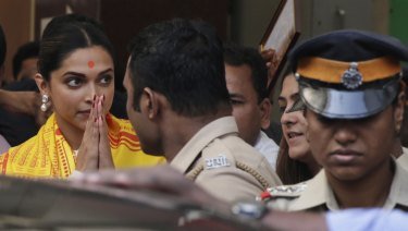 "Bollywood actor Deepika Padukone, left, leaves after offering prayers at a Hindu temple ahead of the release of her upcoming film ""Padmaavat"" in Mumbai, India."